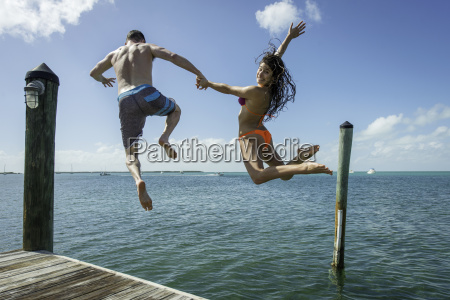 rear view of young couple jumping