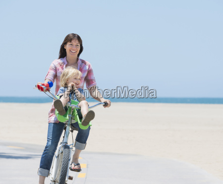 woman and son cycling on beach