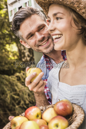 couple outdoors holding apples