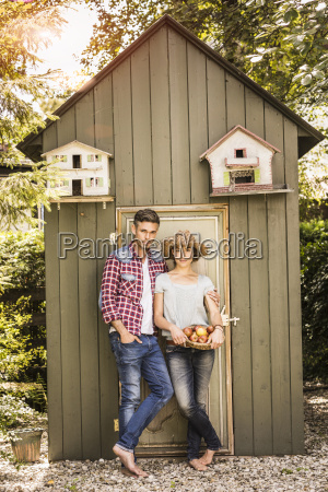 portrait of couple leaning against shed