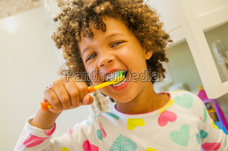 portrait of smiling girl brushing teeth