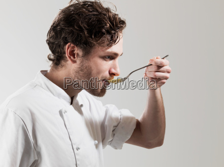 chef tasting food from spoon against