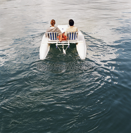 couple on peddling boat on water