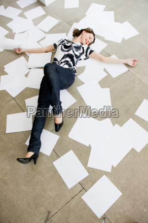 woman lying between sheets of paper