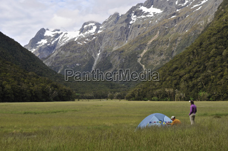 couple camping in field with mountains