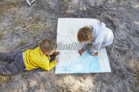 boys reading map on gravel road