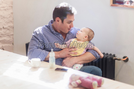 father feeding baby daughter