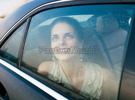 smiling woman looking out car window