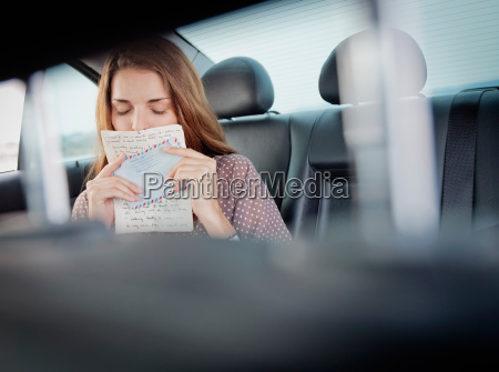 woman kissing letter in backseat of
