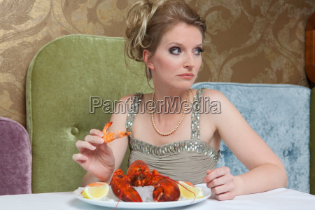 woman in evening gown eating lobster