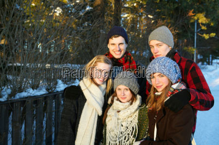 smiling teenagers in winter landscape