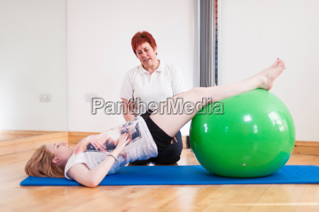 young woman exercising with fitness ball
