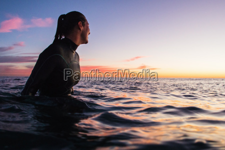 female surfer wading in sea at