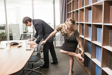 woman putting on shoe and man