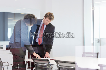 businessmen standing at conference room table