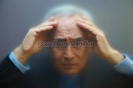 senior man peering through frosted glass
