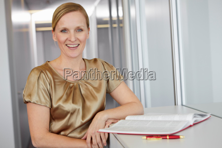 mid adult woman standing beside book