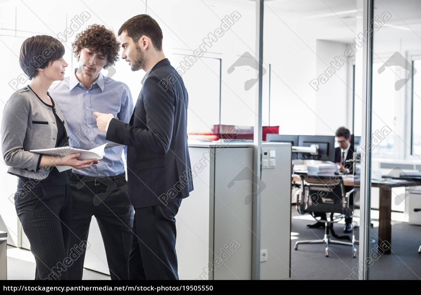 wirtschaftler, die, im, büro, betrachtet, schreibarbeit, stehen - 19505550