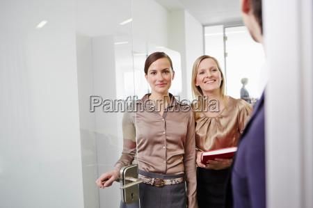 women wearing business attire standing in