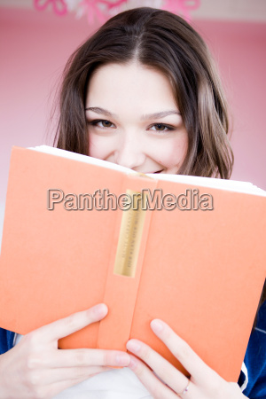 girl looking at viewer with book