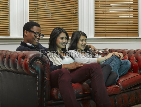 three young adult friends sitting on