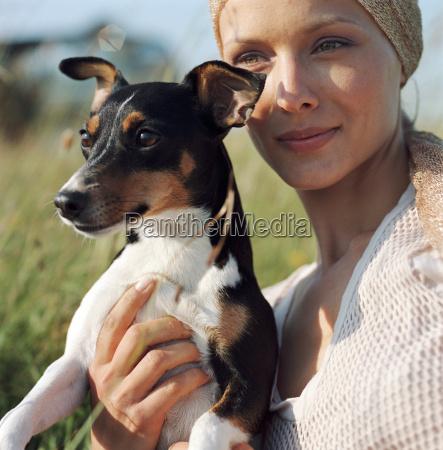 woman with dog among long grass