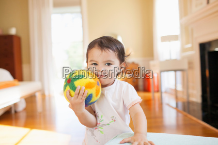 smiling baby girl pressing yellow floral