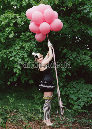 woman wearing clown outfit holding balloons