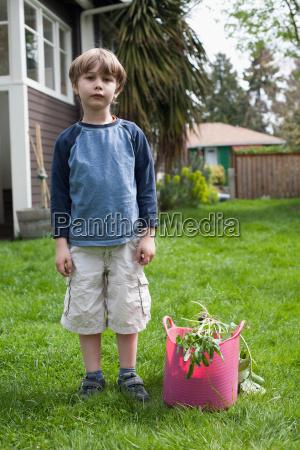 boy standing in garden next to