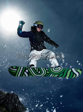 female snowboarder jumping over rock