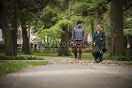 couple walking dog in park savannah