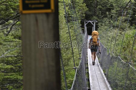 woman crossing footbridge new zealand