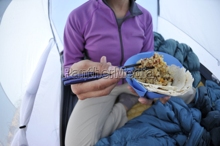woman eating food in tent