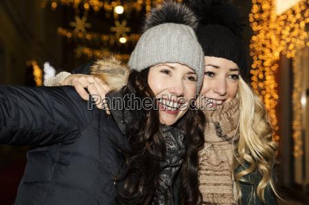 two mid adult women wearing hats