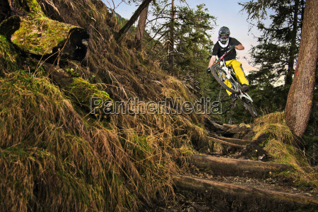 male mountain biker riding down forest