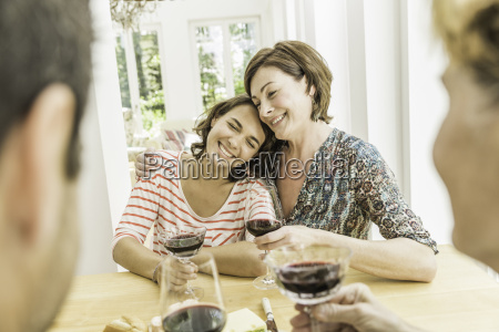 four adult friends drinking red wine