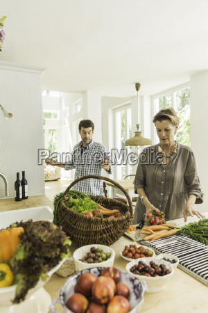 couple preparing fresh vegetables on kitchen