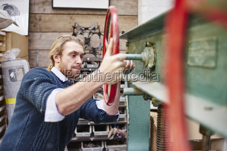 young man turning print press wheels