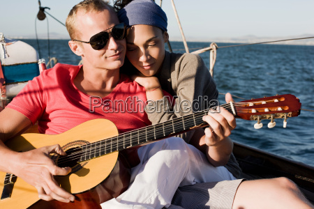couple on yacht man playing guitar