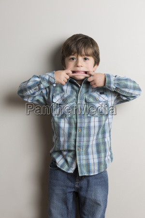 portrait of young boy making funny