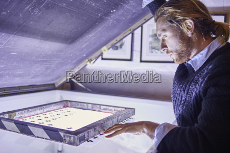 young man preparing screen on lightbox