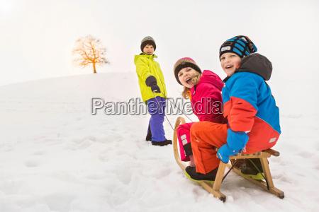 boy pulling two friend through snow