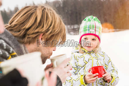 father and daughter drinking hot drinks