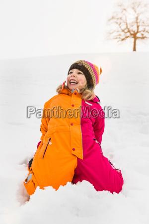 portrait of girl wearing snowsuit kneeling