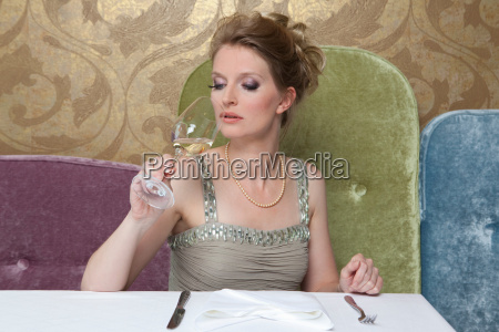 woman in evening gown drinking wine