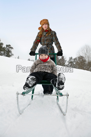 young woman pushing boy on sled