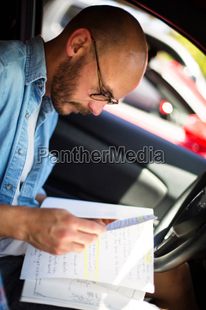 mid adult man reading notes in