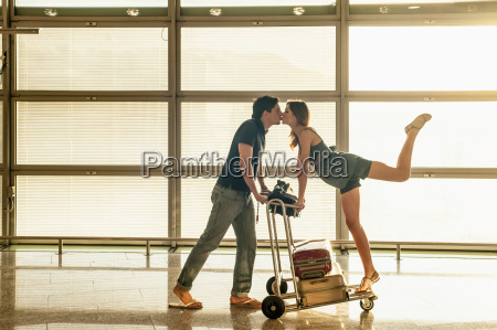 young couple with luggage trolley kissing