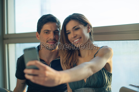 young couple photographing themselves on smartphone