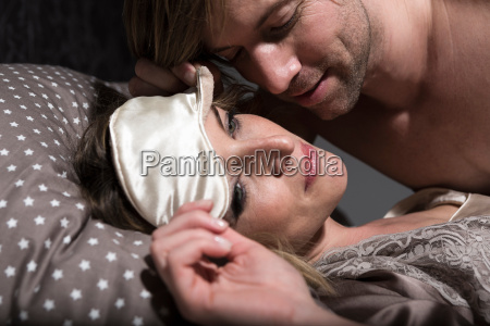 couple in bed woman wearing eye